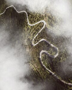 Aerial shot of roads winding through a hill, with clouds above